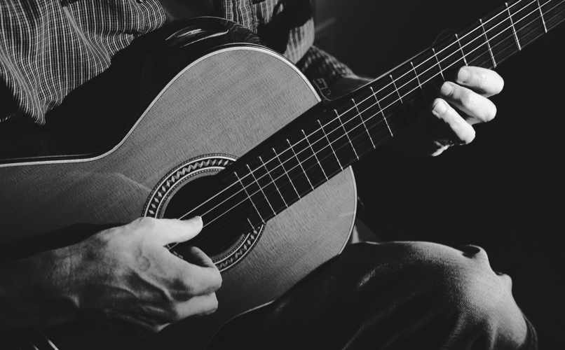 Close up image of a guitarist playing a nylon string guitar.