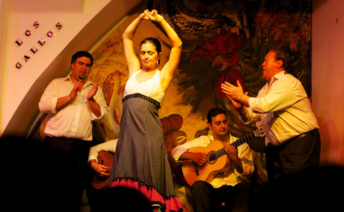 Flamenco performers including a dancer, palmeros, and guitarists.