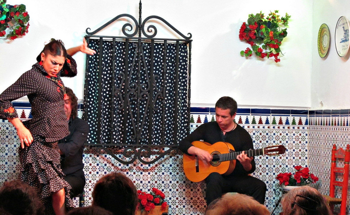 Flamenco dancer and guitarist performing in a small venue.
