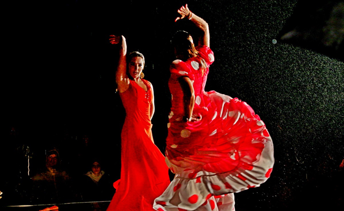 Two flamenco dancers in red in a dramatic pose against a black background.