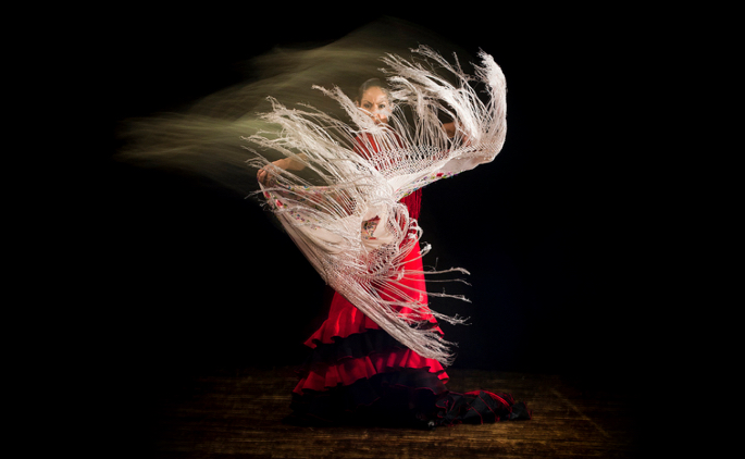 Flamenco dancer with a manton (shawl) in motion against a black background.