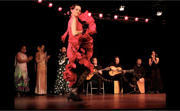 Flamenco dancer in a red dress performing footwork on stage with musicians and singer singers in the background.