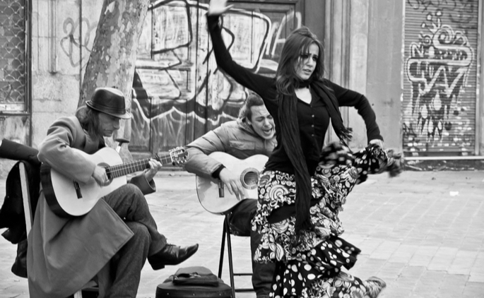 A dancer performing with two guitar players outdoors on the street with graffiti on the walls in the background.