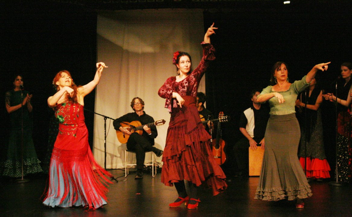 Three dancers performing on stage with musicians in the background.